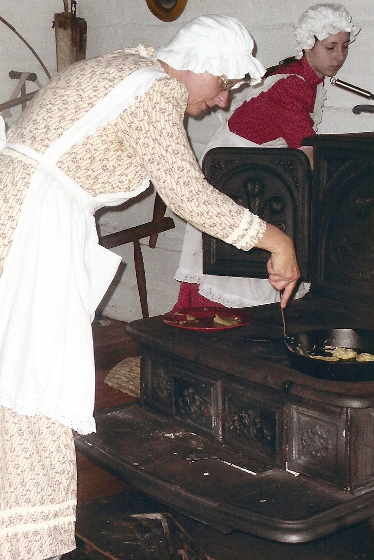 Two pioneer costumed women baking on an old cast iron stove